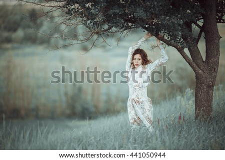 Young girl in vintage dress standing near lonely tree