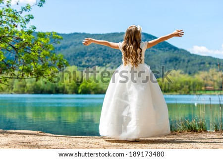 Young girl in white communion dress with open arms at lake. - stock photo