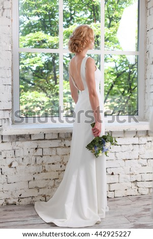 young girl in white dress. beautiful bride in a white dress holding bouquet of flowers and standing near a large window. wedding day