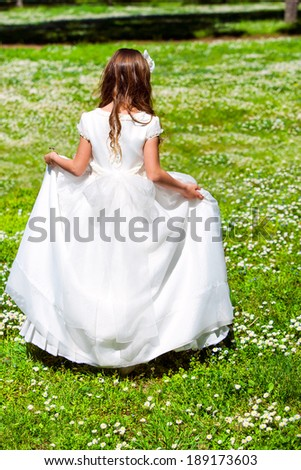 Young girl in white dress walking in flower field.