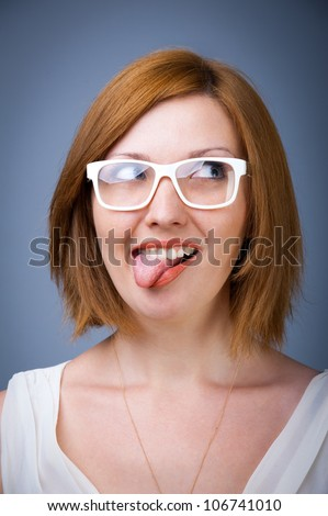 young girl in white glasses in a good mood with his tongue hanging out - stock photo