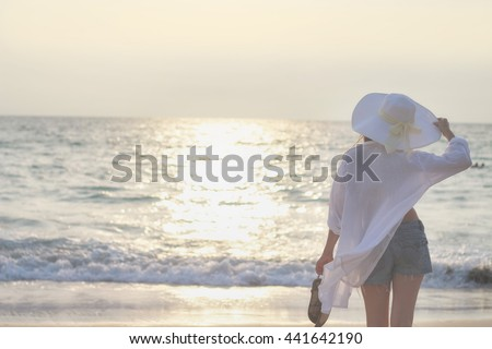 Young girl in white hat and shorts watching the sunset at the ocean