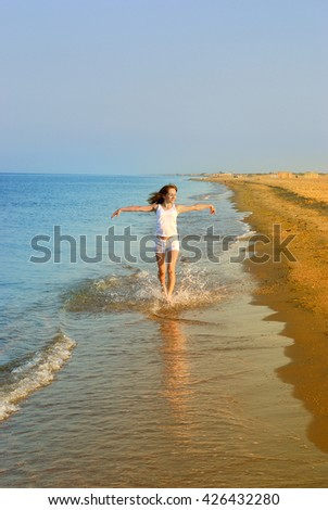 Young girl in white running on seashore - stock photo