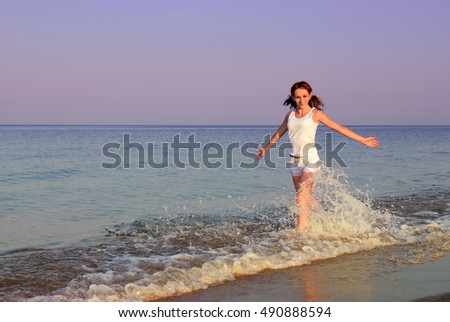 Young girl in white running on seashore
