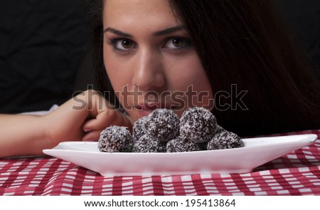 Young girl in white shirt eating chocolate balls with coconut on them - stock photo