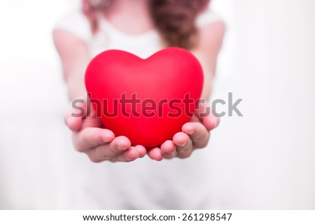 young girl in white shirt with l red heart