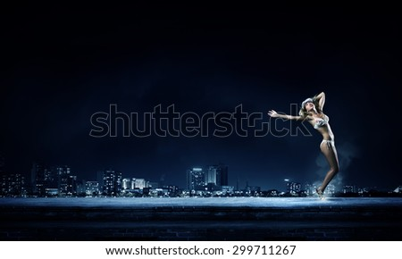 Young girl in white swim wear dancing in night