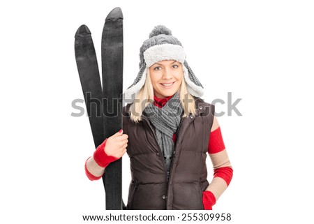 Young girl in winter clothes holding skis isolated on white background - stock photo