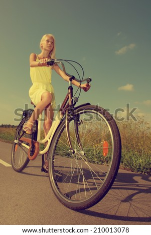 Young girl in yellow dress riding a retro style bike. - stock photo