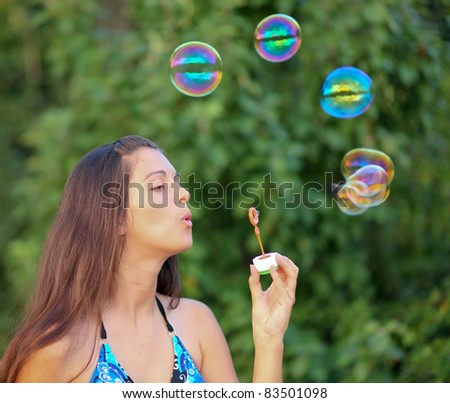Young girl inflating colorful soap bubbles