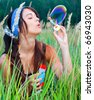 Young girl inflating soap bubbles - stock photo