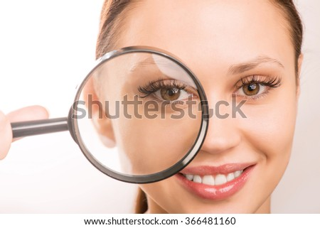Young girl is holding a loupe at her eye.