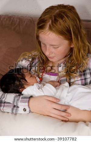young girl  is holding her 3 weeks old baby niece - stock photo