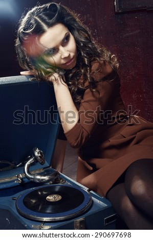 Young girl is listening music with gramophone