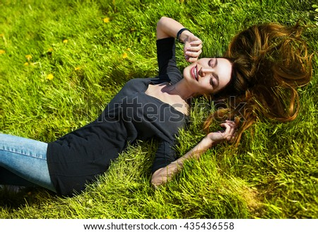 Young girl is lying on green grass