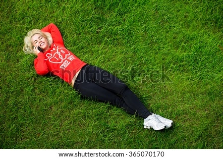 Young girl is lying on green grass talking on the phone - stock photo