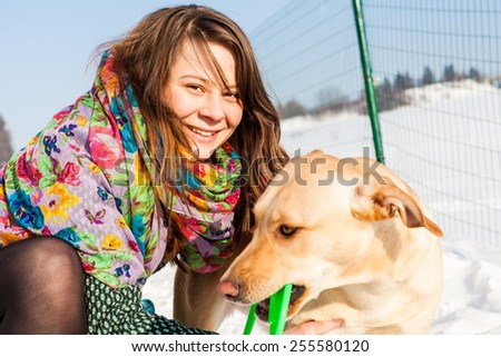 Young girl is playing with her dog and green toy - stock photo