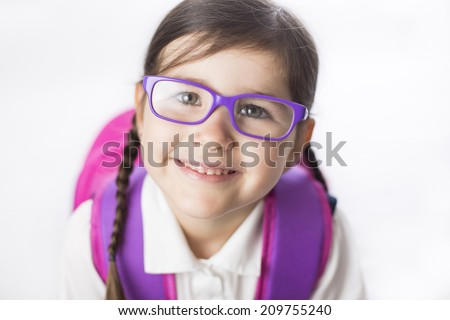 Young girl is ready to start school in a uniform wearing a backpack.  - stock photo