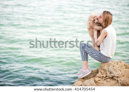 Young girl is resting with a dog on the sea. - stock photo