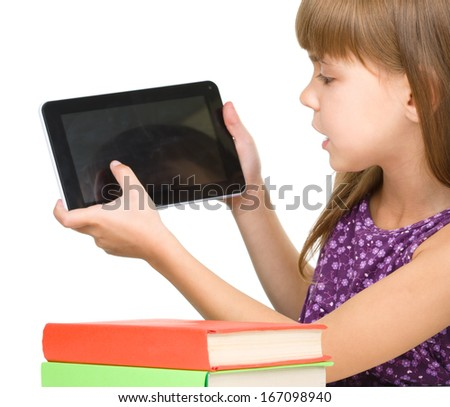 Young girl is showing tablet while sitting at table, isolated over white - stock photo