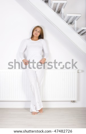 Young girl is sitting by a white heater - stock photo