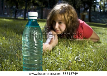 Young girl is trying to reach for a bottle - stock photo