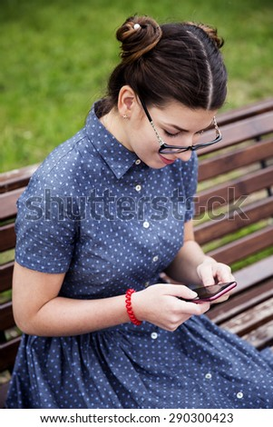 Young girl is using smart phone, sitting on the bench in the park.