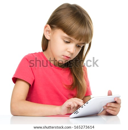 Young girl is using tablet while sitting at table, isolated over white