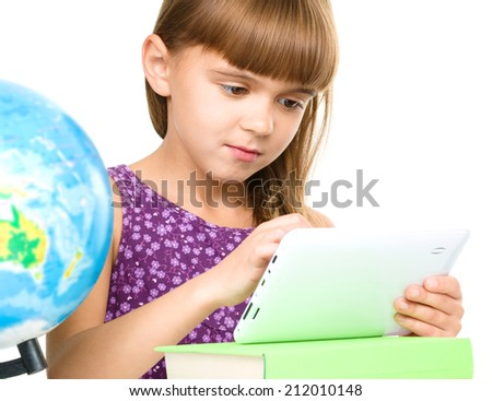 Young girl is using tablet while sitting at table, isolated over white - stock photo