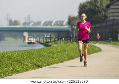 Young girl jogging near the river embankment. Healthy lifestyle.