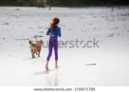 young girl jogs with a dog along the beach - stock photo