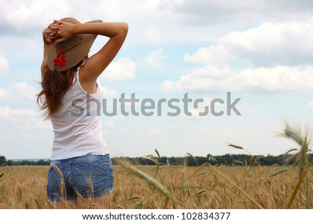 young girl joys on the wheat field with blue cloudy sky at the background