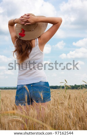 young girl joys on the wheat field with blue cloudy sky at the background. - stock photo