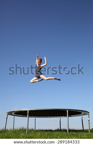 Young girl jumping on a trampoline on green meadow