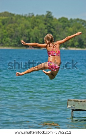 Young Girl Jumps Off Dock into Lake  Extending Arms and One Leg - stock photo