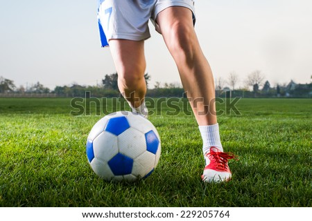young girl kicking soccer ball on field - stock photo