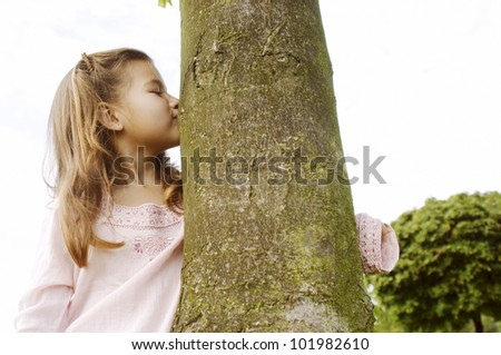 Young girl kissing a tree trunk in the park. - stock photo