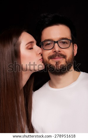 Young girl kissing her boyfriend on the cheek. Boyfriend and girlfriend. - stock photo