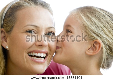 Young girl kissing smiling woman - stock photo
