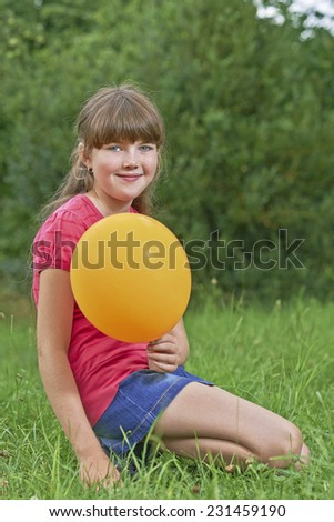 Young girl kneeling on the grass with balloon - stock photo