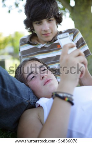Young girl laid on the grass with a phone near a boy