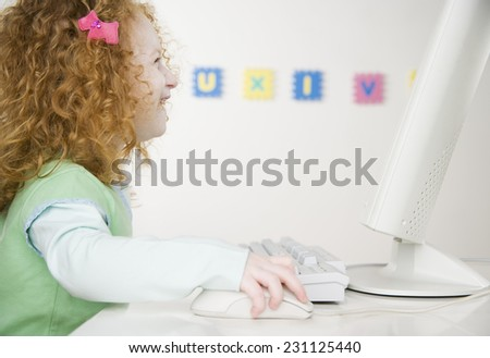 Young Girl Laughing as She Plays on the Computer
