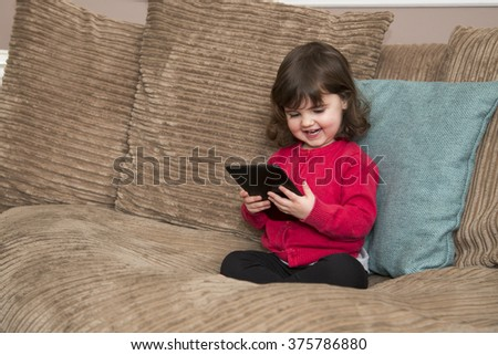 Young girl laughs at tablet screen - stock photo