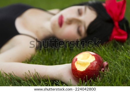 Young girl laying on grass holding a poison apple - stock photo