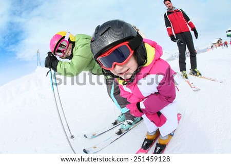 Young girl learning how to ski with family - stock photo