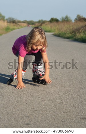 young girl learning to skate on her inline roller skates