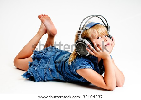 Young girl listen to music in headphones on white background - stock photo