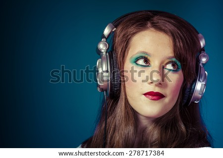 young girl listening music with huge headphones - stock photo