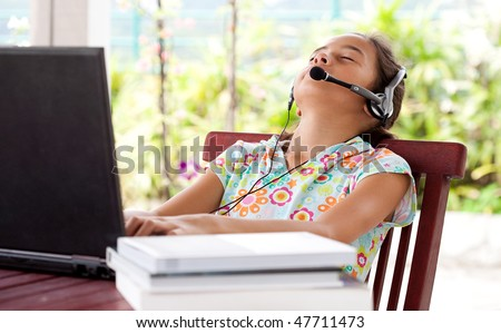 Young girl listening to headphone while on laptop computer, resting her head on chair. - stock photo