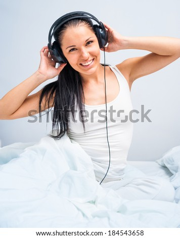 young  girl listening to music at home in white bed - stock photo